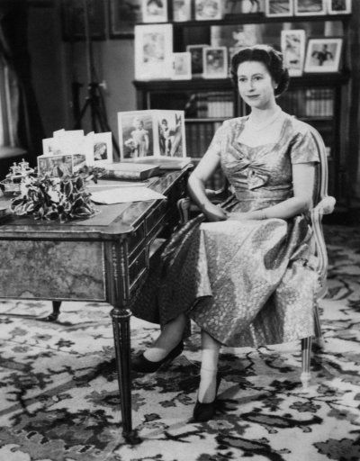The Queen, in a gold lame dress, is seen in the Long Library at Sandringham shortly after making the traditional Christmas Day broadcast to her peoples. On the desk are portraits of Prince Charles and Princess Anne. The broadcast was televised this yer for the first time and was carried by both the BBC and ITV. It was the 25th anniversary of the first radio message to the Commonwealth by her grandfather, King George V.